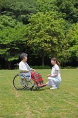 公園で休む車いすのシニア女性と介護福祉士