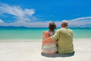 Happy senior caucasian couple sitting near the sea  and hugging.