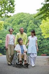 公園を散歩するシニアの男女と介護福祉士