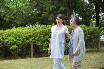 シニア女性の歩行を介助する介護福祉士
