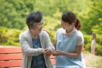 公園のベンチで話すシニア女性と介護福祉士