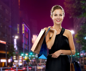 smiling woman in evening dress with shopping bags