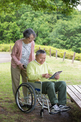 公園でタブレットを見る老夫婦