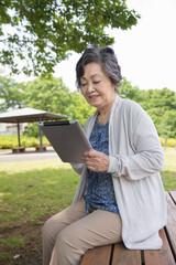 公園でタブレットを見るシニア女性
