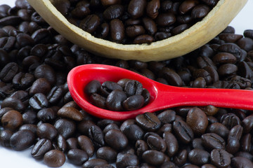 close up of coffee beans inside red spoon