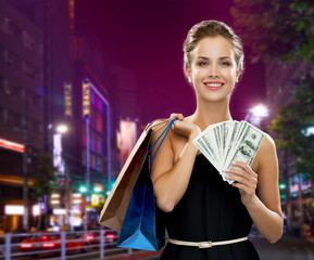 smiling woman with shopping bags and money