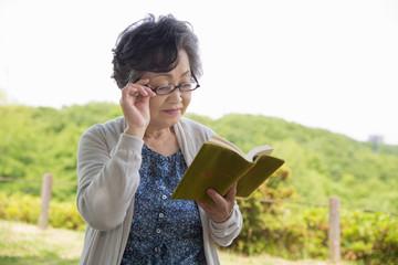 公園で本を読むシニア女性