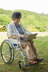 公園で車椅子上でパソコンを使うシニア女性