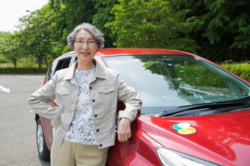 車の横に立つシニア女性