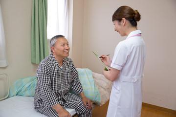 看護師と話すシニアの男性患者