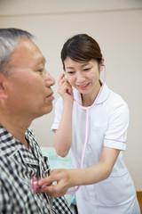 シニアの男性患者に聴診器をあてる看護師