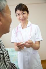 体温計を見る看護師とシニアの男性患者
