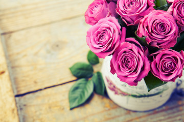 Bouquet of beautiful pink roses on wooden background, toned.
