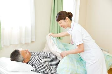 シニア男性患者に布団をかける看護師