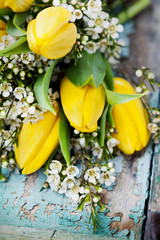 Bouquet of yellow tulips on wooden background, selective focus