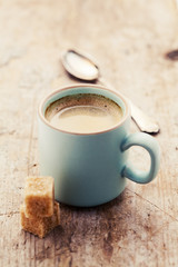 Cup of coffee on wooden table, toned