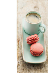 Cup of coffee and macaroons on wooden table.
