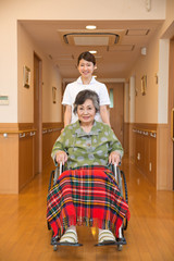 シニア女性患者の車いすを押す看護師