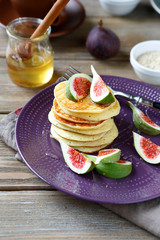 Pancakes with figs and honey on a plate