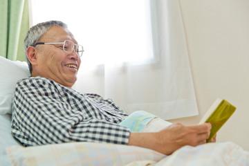 ベッドで本を読むシニア男性患者