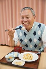 老人ホームで食事を楽しむシニア男性