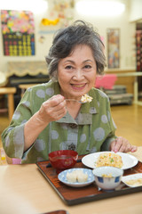 老人ホームで食事を楽しむシニア女性