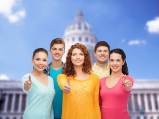 group of smiling teenagers showing ok sign