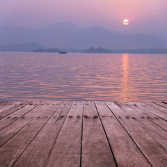 plank board with lake in sunset as background