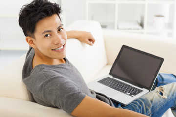 young asian Man sitting in sofa and using  laptop
