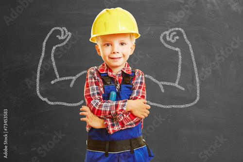 Leinwanddruck Bild Kind als Handwerker mit Muskeln auf Tafel