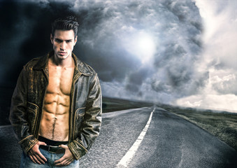 Young man walking down a road with a storm and very bad weather