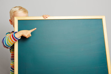 Kind zeigt mit Finger auf Tafel