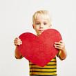 Niedliches Kind mit einem großen roten Herz