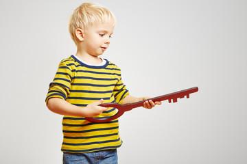 Kind hält einen großen Schlüssel in der Hand