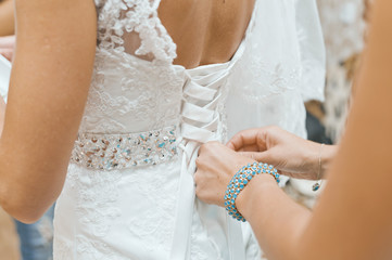 helping the bride with her dress