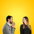 Men pleading at his girlfriend over yellow background