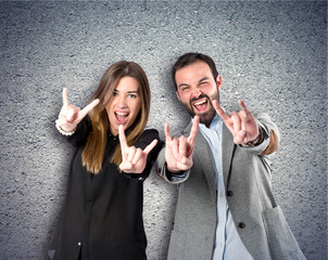 Couple doing the horn sign over textured background