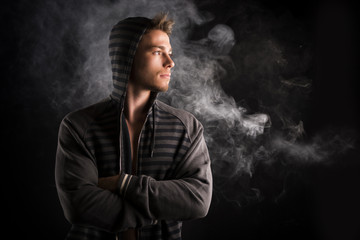 Portrait of handsome tough young man in dark hoodie
