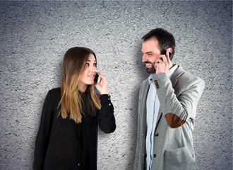 Couple talking to mobile  over textured background
