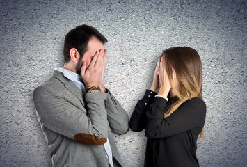 Couple covering their eyes over textured background