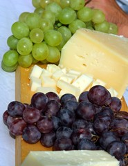 cheese and grapes on the wooden cutting board