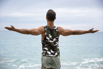 Muscular young man on the beach seen from the back, with arms op