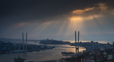 Vladivostok cityscape, sunset with sun rays in the sky.