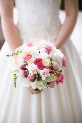 Bride is holding a beautiful delicate pink bridal bouquet