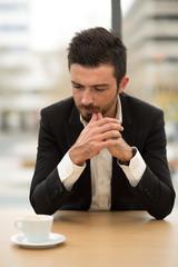 Junger Geschäftsmann wartet beim Kaffee im Büro