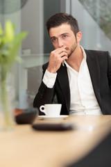 Junger Geschäftsmann grübelt beim Kaffee