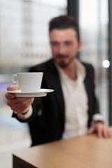 Junger Geschäftsmann reicht Kaffeetasse