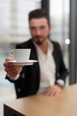 Junger Geschäftsmann reicht Kaffeetasse Hochformat