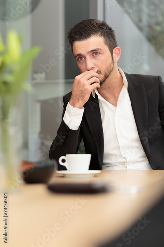 canvas print picture Junger Geschäftsmann grübelt beim Kaffee