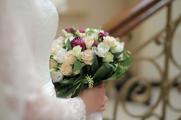 violet and white wedding bouquet of roses in the hands of the br